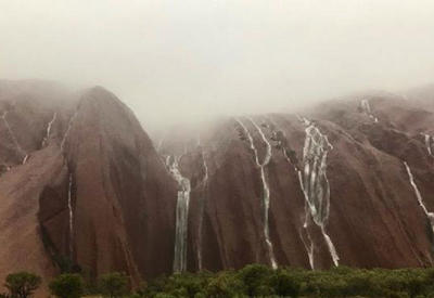 В Австралии ливни превратили священную скалу в водопад