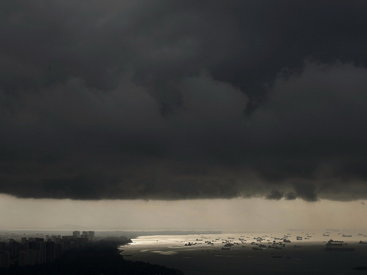 Vessels anchor in the sea as storm clouds gather over the east coast of Singapore