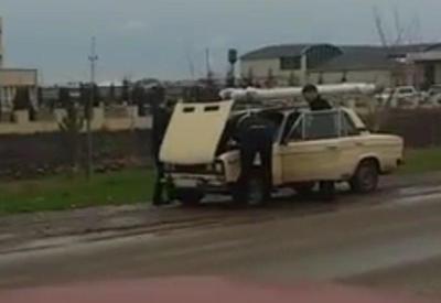 Yol polisləri yolda qalan avtomobili təmir etdi