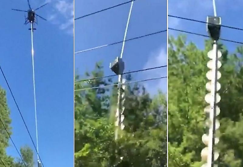 Пилот, привязав к вертолёту огромную бензопилу, обрезал ветви деревьев возле ЛЭП