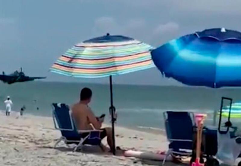 Военный самолет приземлился на пляже в нескольких метрах от отдыхающих
