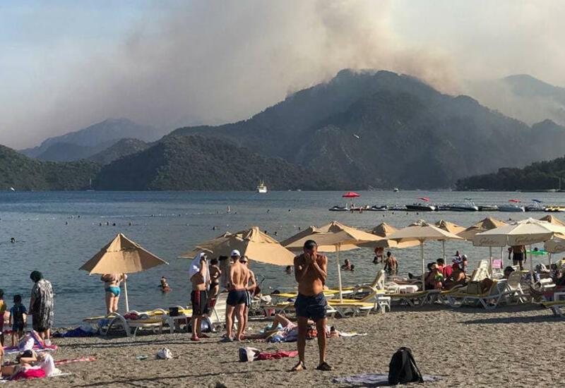 Туристы продолжают плавать в море, несмотря на лесные пожары в Турции