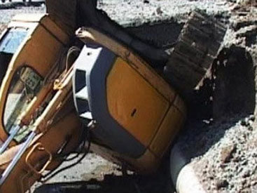 Экскаватор упал со здания на дорогу в центре Баку