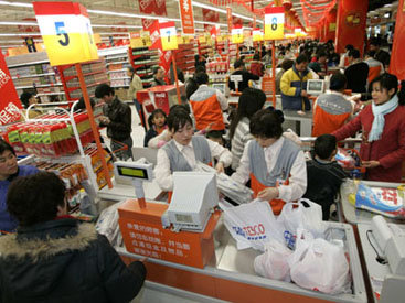 Customers pay at cashiers at a newly opened Tesco supermarket in Beijing